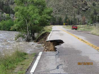 Near Picnic Rock, at the mouth of the Poudre Canyon, the flood-swollen river undercut Colorado Highway 14. Photo by Diane Sanford of Poudre Park.